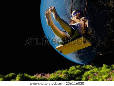 "Girl on a swing on the background of the planet. ""Elemen ts of this image furnished by NASA"" - stock photo"