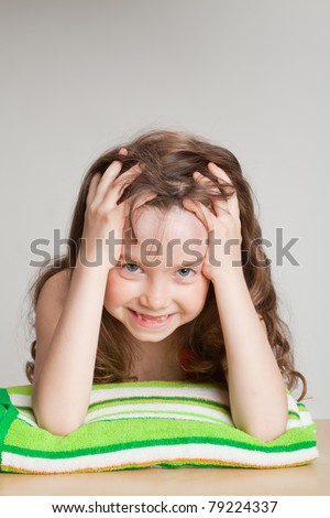 Girl on a towel, smiling with baby teeth dropped out, his head in his hands - stock photo