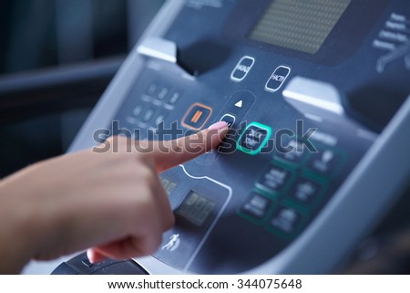 girl on a treadmill presses the button