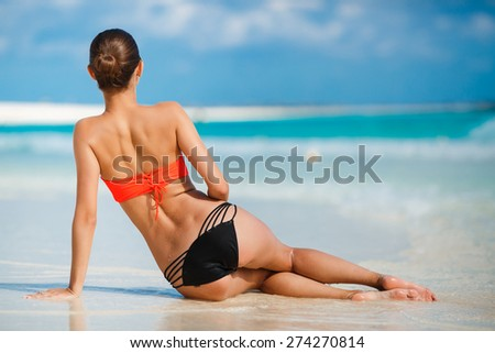 Girl on a tropical beach. Beautiful girl sitting on the beach near the ocean. beautiful woman sitting from the back on beach. - stock photo