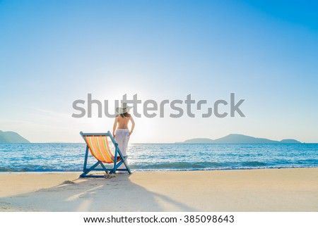 Girl on a tropical beach with a straw  hat