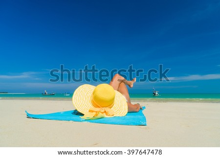 Girl on a tropical beach with a yellow hat - stock photo