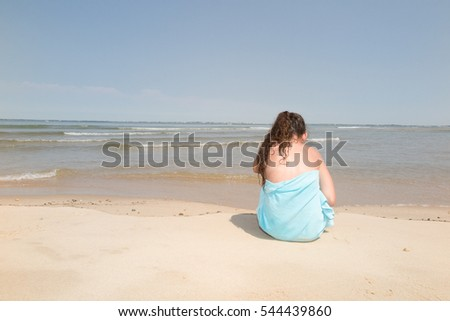 Girl on a tropical beach with green towel