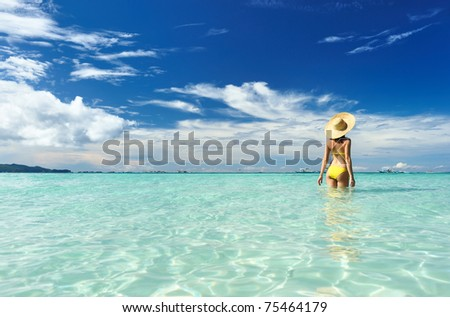 Girl on a tropical beach with hat - stock photo