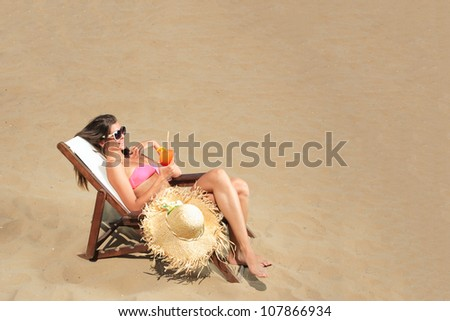 Girl on a tropical beach with hat and sunglasses holding a cocktail - stock photo