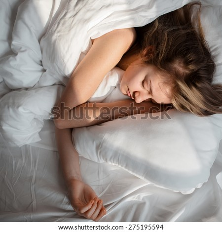 Girl on a white pillow in the morning - stock photo