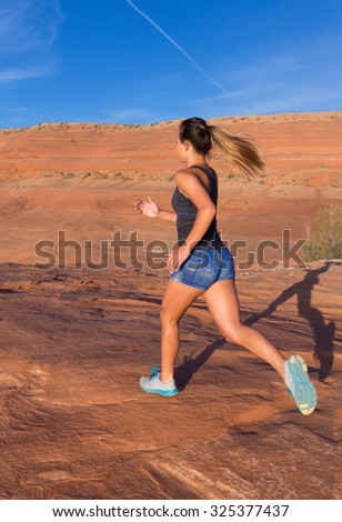 Girl on an early morning run surrounded by the orange colored rocks of Southern Utah.