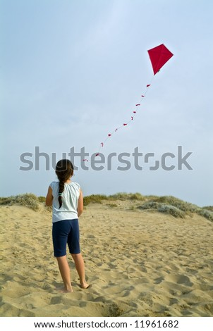 girl on beach playing with a red kite - stock photo
