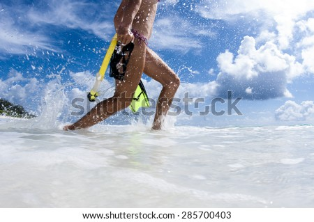 Girl on beach running into ocean to go snorkelling