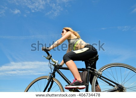 Girl on bike in sunny day. - stock photo