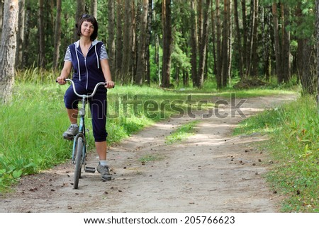 girl on bike on a forest road