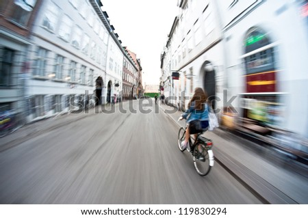 Girl on bike riding fast - motion blur - stock photo