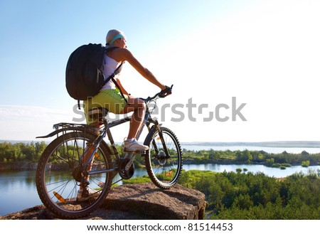 Girl on bike stands high on a hill and looks forward to the natural open spaces