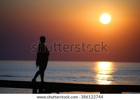 Girl on bridge against the sunset at the sea.