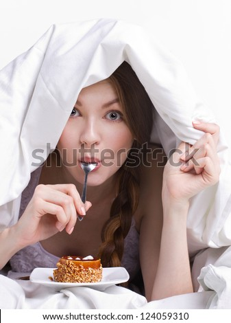 girl on diet eating spoon instead of dessert  under white cover on white background - stock photo