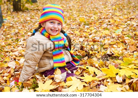 girl on fall autumn leaves in park - stock photo