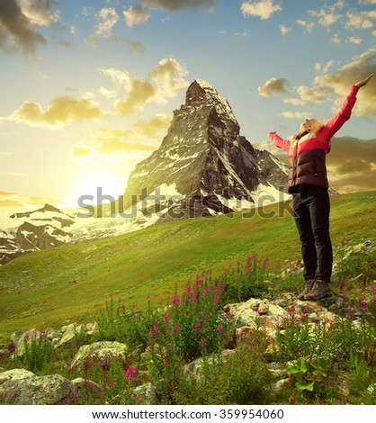 Girl on meadow, in the background mount Matterhorn - Swiss Alps, Europe - stock photo