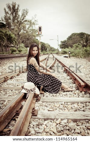 Girl on railway sitting with her hat process in vintage style - stock photo