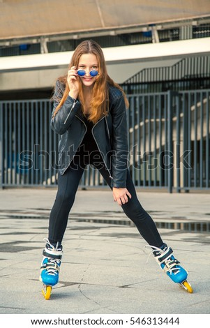 Girl on rollerblades standing in building background. Young fit women girl in blue sunglasses, jeans and jacket on roller skates riding outdoors after rain.