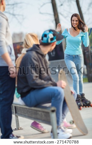 Girl on rollerblades waving to her friends sitting in a skate park waiting for her - stock photo