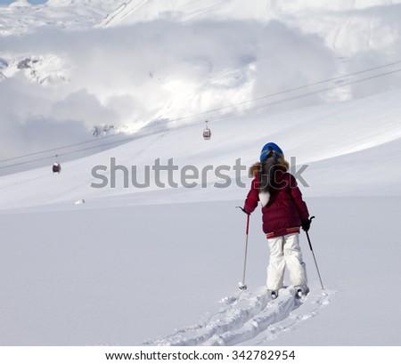 Girl on skis in off-piste slope with new fallen snow at sun day. Caucasus Mountains, Georgia, ski resort Gudauri. - stock photo