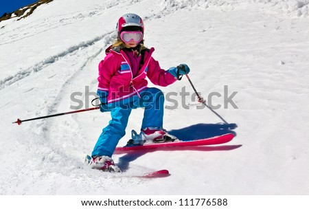 Girl on skis in soft snow on a sunny day in the mountains, on a steep slope. - stock photo