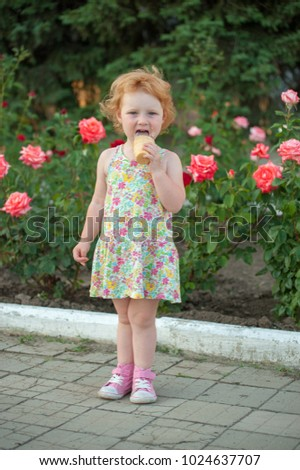 Girl on the background of flowers eating ice cream
