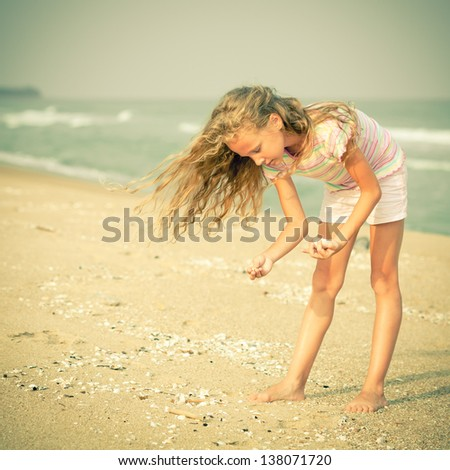 girl on the beach collecting shells - stock photo