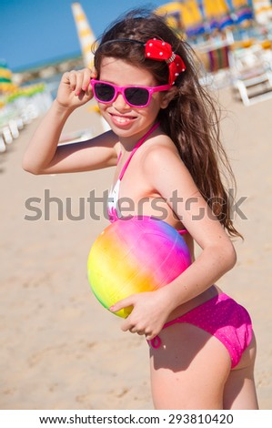Girl  on the beach holding a volleyball ball - stock photo