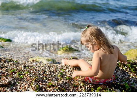 girl on the beach playing with pebble - stock photo