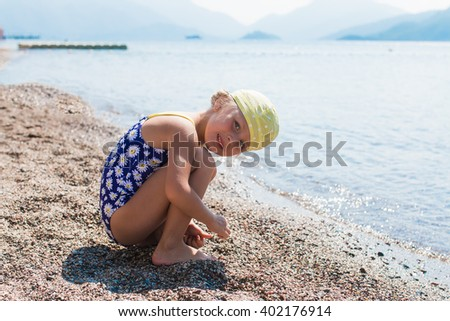 girl on the beach playing with sand and shells on the beach on a sunny day