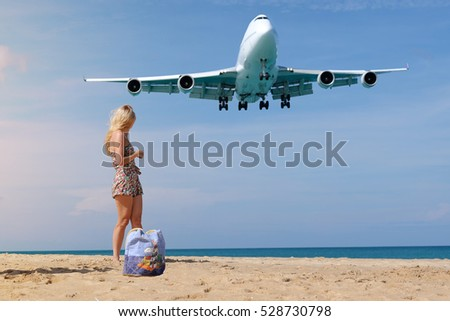 Girl on the beach with her bag and airplane landing at Phuket, Thailand