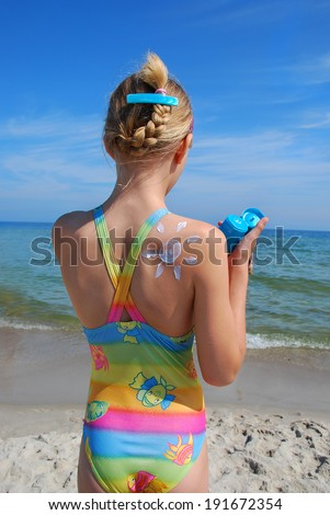 girl on the beach with the sun shape painted by suntan lotion on the skin - stock photo