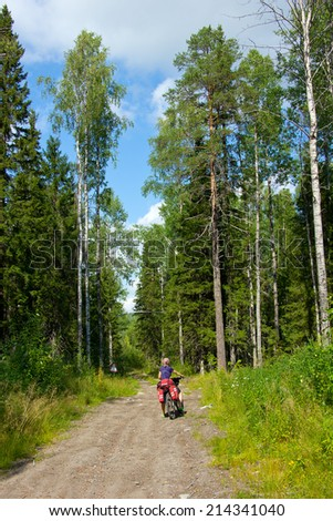 girl on the bicycle between tall trees, road sign in the background, Russia, Karelia, 2014 - stock photo