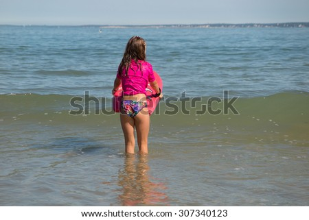 Girl on the board at the ocean surfing