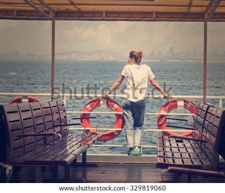 girl on the boat, watching the sea - stock photo
