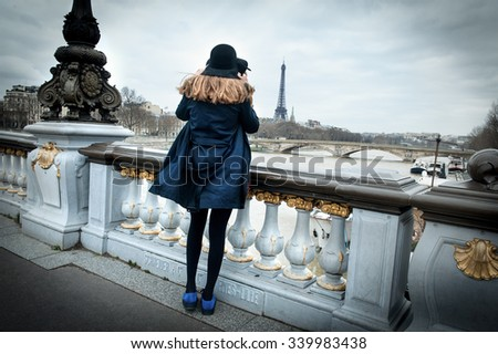 Girl on the Bridge of Alexander the third, looking at the wall. Paris - stock photo