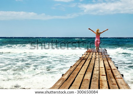 Girl on the bridge pier seashore - stock photo