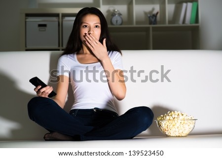 girl on the couch covered her mouth, emotional worries about what is happening on the screen - stock photo