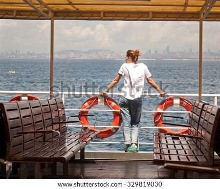Girl on the deck, watching the sea - stock photo