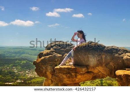 Girl on the edge of a mountain looking at the landscape