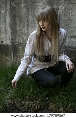 girl on the lawn, Pretty girl plugs on the lawn in front of a concrete wall