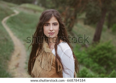 Girl on the nature. Dressed in a denim skirt and suede jacket.