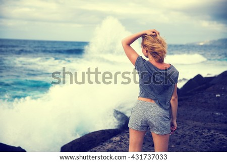 girl on the ocean watching the big waves