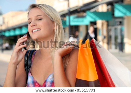 girl on the phone after shopping frenzy - stock photo