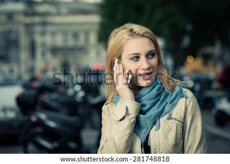 Girl on the phone, her scooter on the background - stock photo