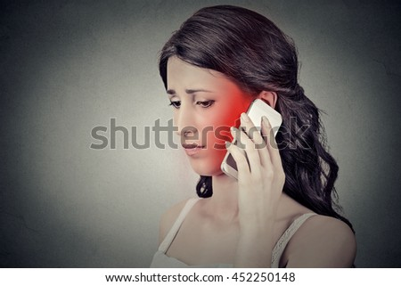 girl on the phone with headache. Upset unhappy female talking on phone isolated grey wall background. Negative human emotion face expression feeling life reaction. Cellular mobile radiation concept