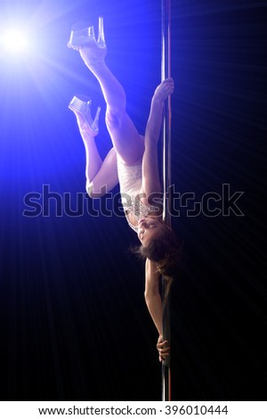Girl on the pole. attractive sexy woman pole dancer performing on stage. Young sexy pole dance woman. pole dancer making stretching figure - stock photo