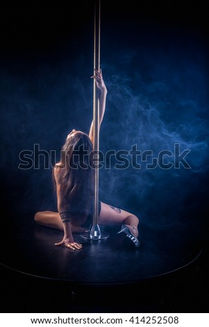 Girl on the pole. attractive sexy woman pole dancer performing on stage. Young sexy pole dance woman. pole dancer making stretching figure