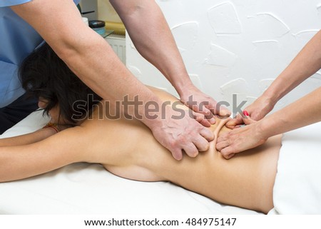 girl on the procedure for four hands massage in the spa salon
